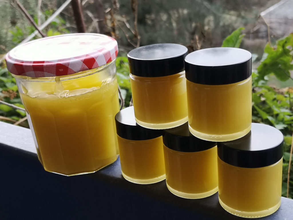 Einige Salbentiegel und ein Marmeladenglas voller selbstgemachter Fichtenpechsalbe stehen zum Abkühlen auf dem Balkongeländer.